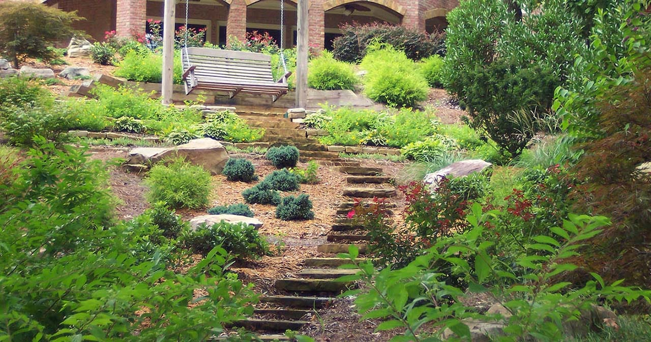 A Landscaped backyard with a stone path and many plants and bushes